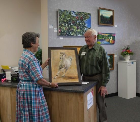 Conrad Young, right, with his wife Penny, left, at the Lakes Region Art Association Gallery in Tilton, NH.