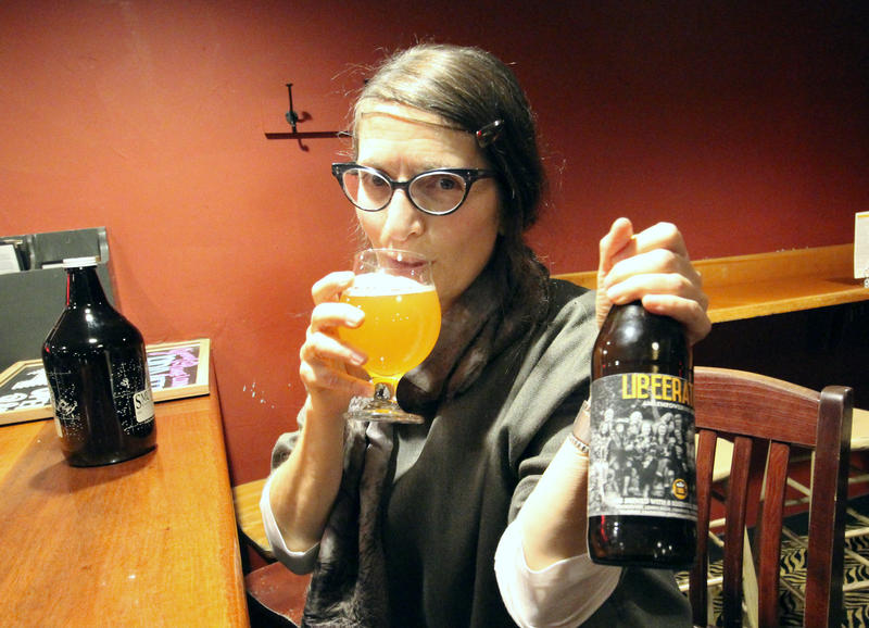 Joanne Francis of Portsmouth Brewery sips and shows off a bottle of Libeeration, a beer made for women experiencing symptoms of menopause.