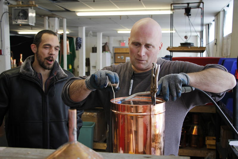 Jon Zajac (left) watches Bobby Jones at the Distillery Network work on a still.
