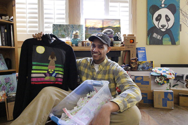 Isidro Rodriguez in his North Haverhill, N.H. apartment with items he's collected for a raffle to support his organization, Food4Kids.