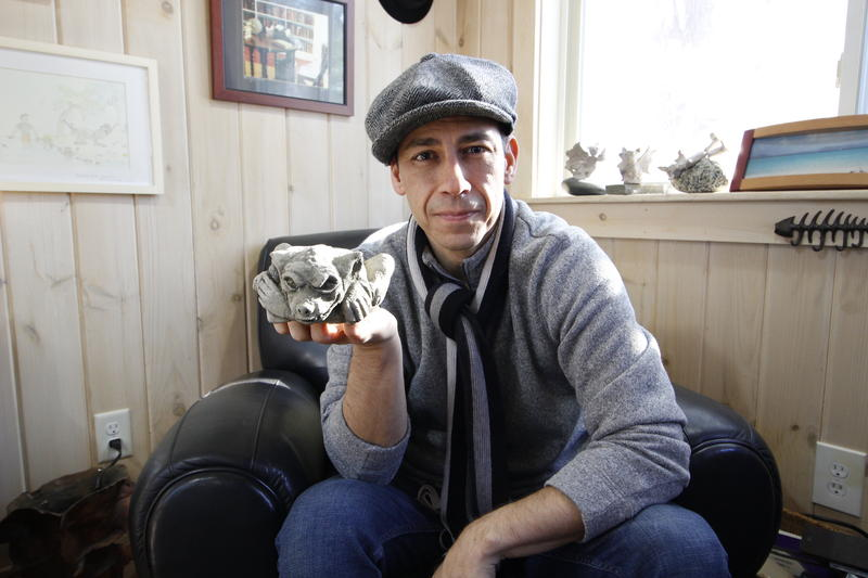 Paul Durham in his writing studio in his backyard in Exeter, N.H. showing off the little stone gargoyle that served as inspiration for the protagonist of his new middle grade novel.