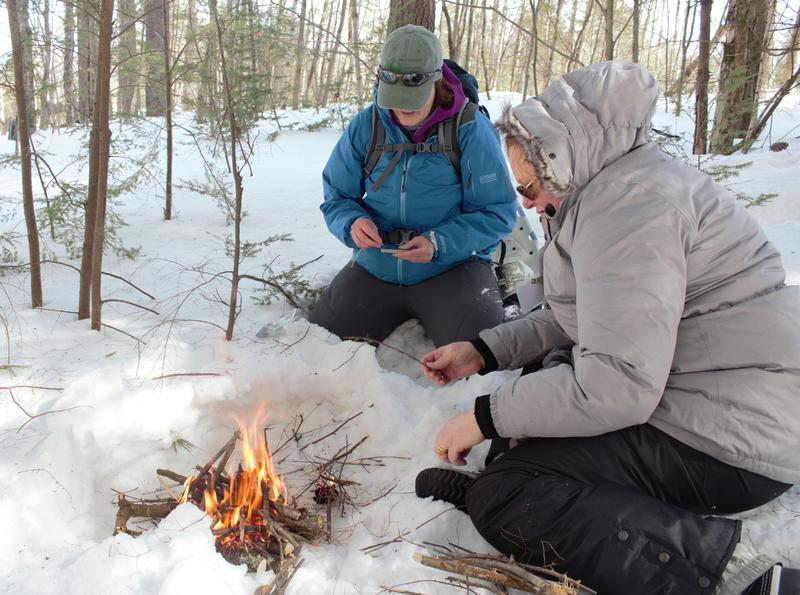 Julia Wilcox and Claire Rouge tend to a fire they made during BOW's winter survival skills class.