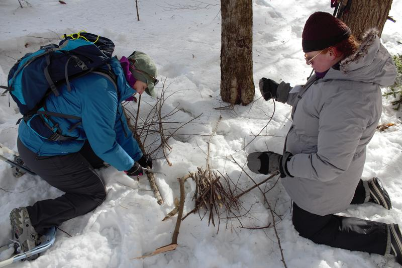 Julia Wilcox and Claire Rouge collect sticks for a fire.