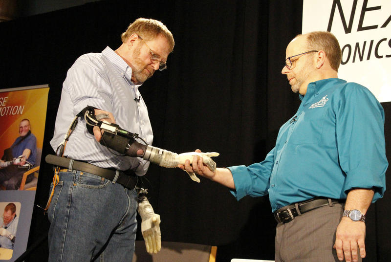 Air Force Veteran Ron Currier (left) shakes hands with Matt Albuquerque of Next Step Bionics & Prosthetics at a demonstration of the technology in Manchester on Thursday, February 22, 2018.