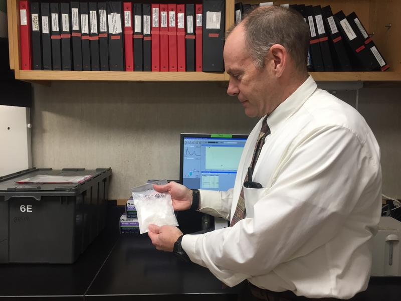 Director of the State's Crime Lab Tim Pifer holds up a bag of meth the lab just analysed. The number of meth cases has increased by 1,500 percent since 2014.