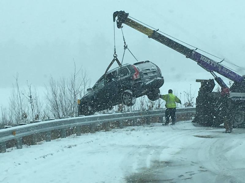 A wrecker retrieves a vehicle that went off the Laconia bypass in Gilford on Tuesday.