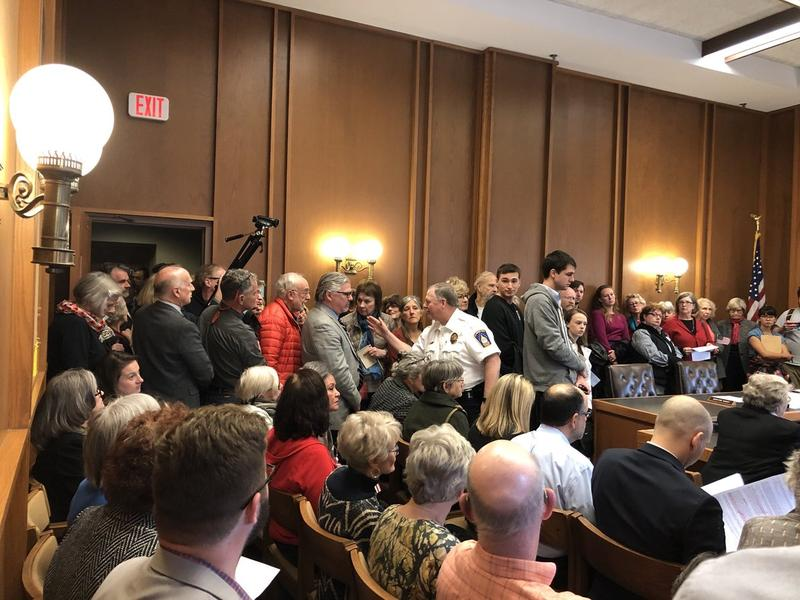 The group of prospective hearing attendees was too large to fit inside the original hearing. At one point, Senators called in assistance from a security guard to keep the crowd contained.