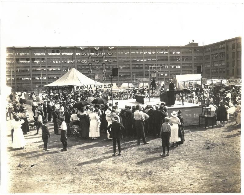 View of McElwain Club Carnival. This view shows the Central Plant with an open air theatre platform.