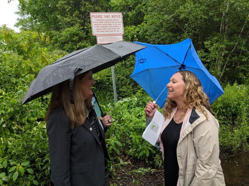 Regional EPA administrator Alexandra Dunn, left, speaks with Coakley neighbor and activist Jillian Lane beside a warning sign at Berry's Brook outside Coakley Landfill.