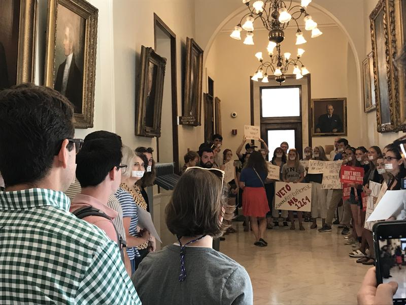 Protesters eneter the State House calling on Gov. Sununu to veto voter residency bill