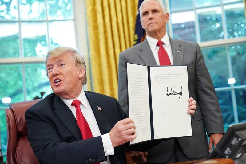 President Trump holds up an executive order on family separation.