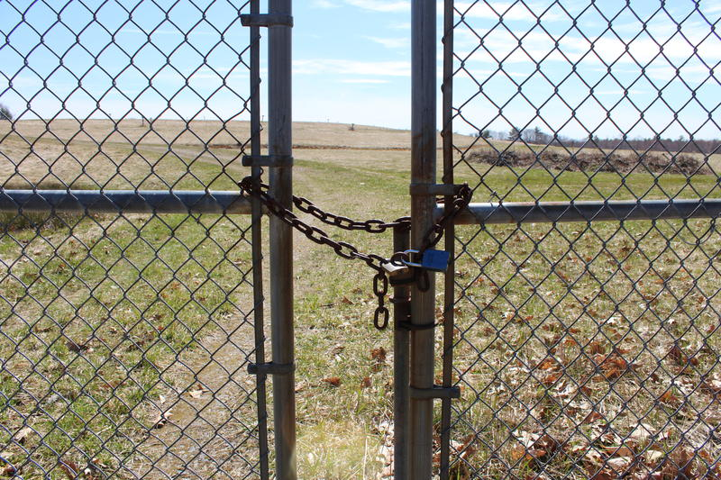 A padlocked gate bars the way to the Coakley Landfill Superfund site in North Hampton.