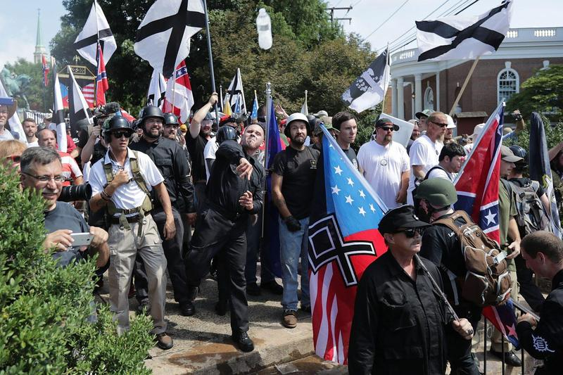 """Hundreds of white nationalists, neo-Nazis, KKK and members of the """"alt-right"""" hurl water bottles back and forth against counter demonstrators on the outskirts of Emancipation Park during the Unite the Right rally Aug. 12, 2017 in Charlottesville, Va. (Chi"""
