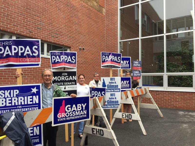Supporters hold campaign signs outside the polls in Exeter