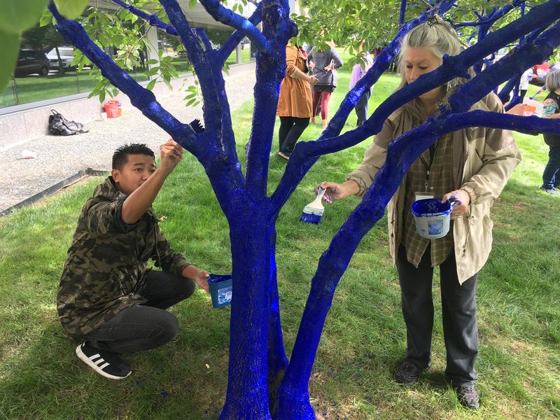 Participants and caregivers from Siddharth Services Inc. paint trees behind the Currier Museum.