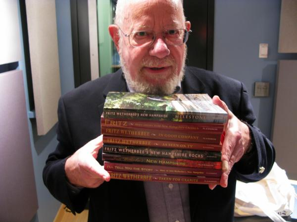 Fritz Wetherbee holds copies of his eight books, totaling one thousand stories about New Hampshire in all.