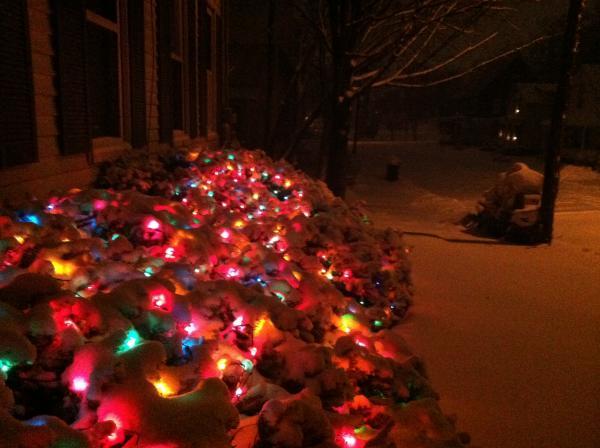 Snow on Christmas lights makes the storm feel festive