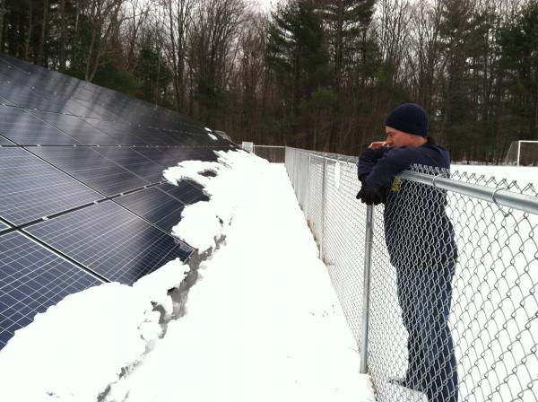 Clay Mitchell of Revolution Energy surveys a solar array his company owns and operates at East Kingston Elementary School. Despite cold temperatures, the panels gave off enough heat that the snow had slid right off.
