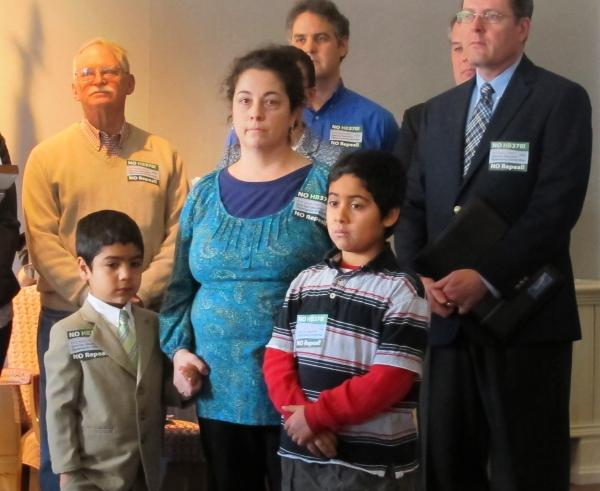 Dominique Vasquez-Vanasse stands with her two sons at a press conference. She testified before the Ways and Means Committee in support of an education tax credit.