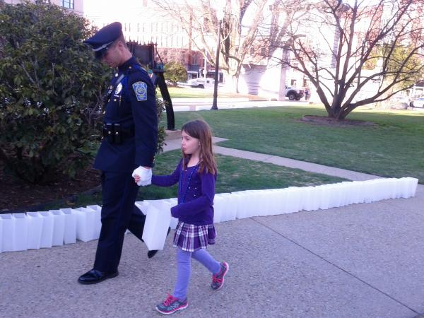A Nashua detective in his dress blues walks girl down luminary-lined walkway towards the state house.