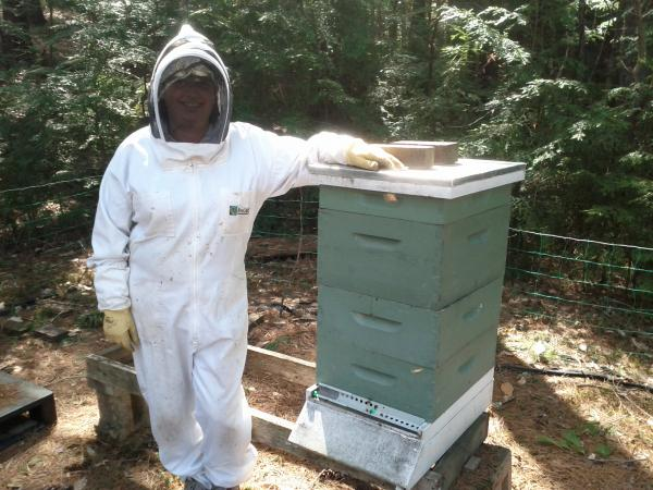 Wendy Booth at a beehive she adopted.