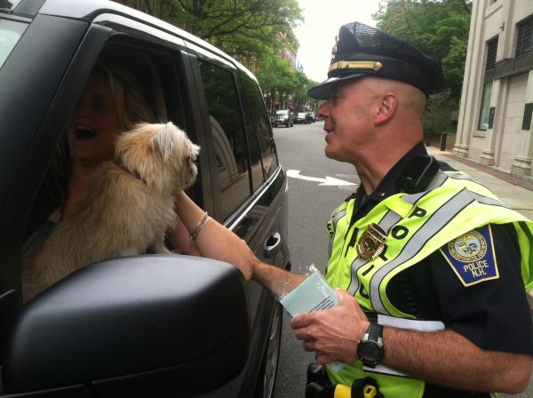 Lt. Jim Flanagan of the Manchester Police Department hands a pamphlet about distracted driving to a woman who was driving with her dog in her lap.
