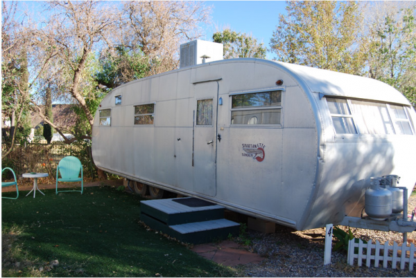 """1950 Spartanette - """"This 30' """"park model"""" was built in 1950. It has rich birch wood interior, twin beds, a small bathroom and a couch in the living room. It has a vintage black and white television and a phonograph with a selection of 45 rpm records."""""""