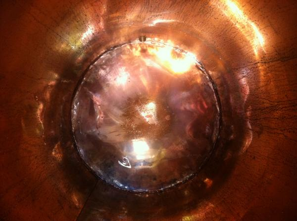 A view inside the 60-gallon copper still before the mash is poured in.