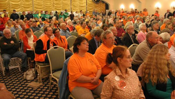 A group of Northern Pass supporters, wearing green and blue, stood at the rear of the meeting room at the Mountain View Grand. Opponents of the project often wear orange.