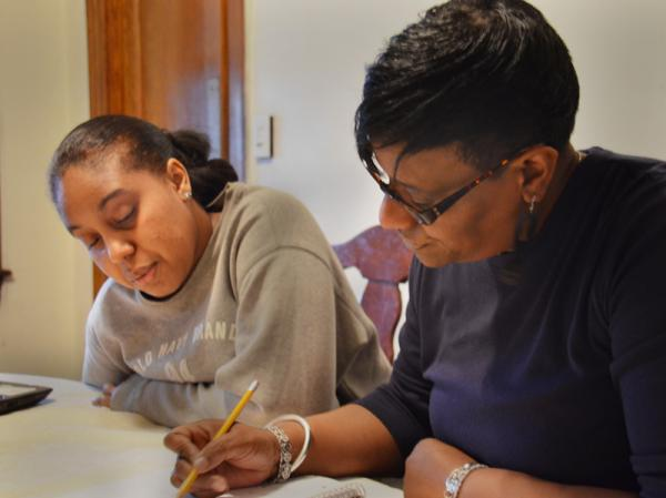 Jean Griggs, GED student, at home with Jalisa Parker, her son's girlfriend. Parker is helping Griggs with her Academy of Hope math homework.