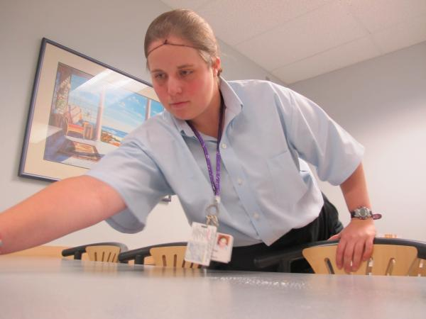 Sara Frost sprays down tables at Portsmouth Regional Hospital's cafeteria.