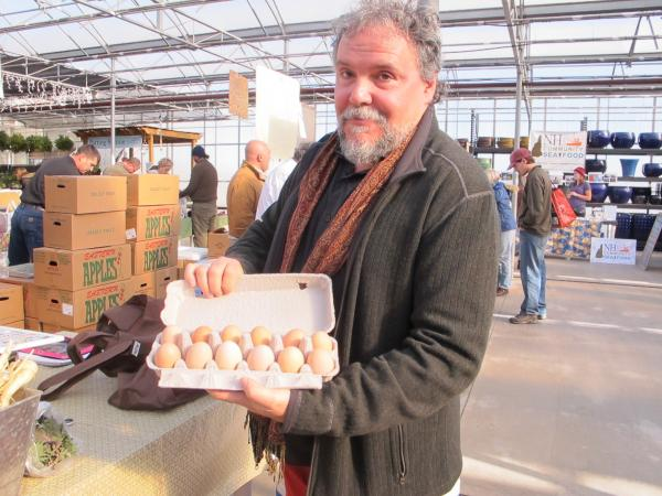 Slow Food Seacoast's John Forti checks out eggs at the Rollinsford Farmers' Market. The group recently put on a Thanksgiving dinner in which ingredients in every dish were harvested no more than 25 miles away.