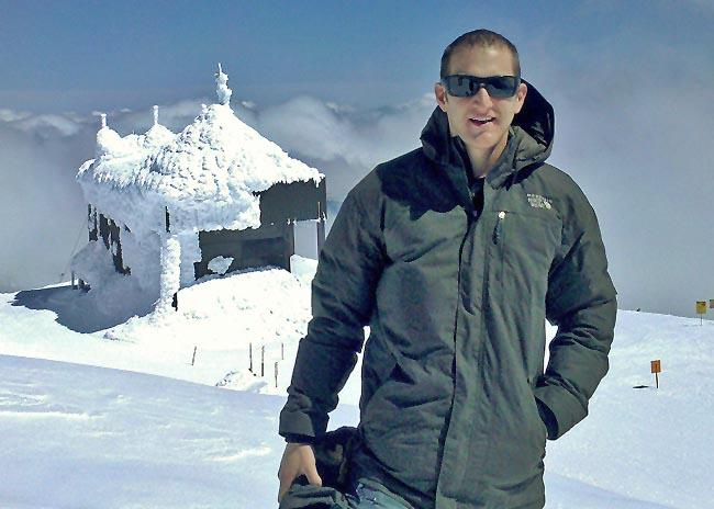 Microbiologist David J. Smith stands atop Mt. Bachelor. Not visible are several thousand species of airborne microbes that he discovered travel across the Pacific Ocean.