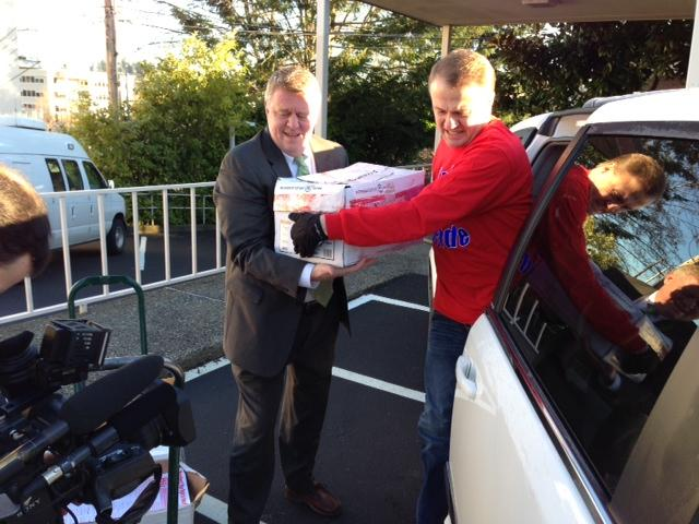 Initiative promoter Tim Eyman (right) unloads boxes of petitions for his latest ballot measure.
