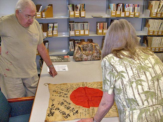 "George Koller (left) shows the ""good luck flag"" to historian Priscilla Wegars of Moscow, Idaho."