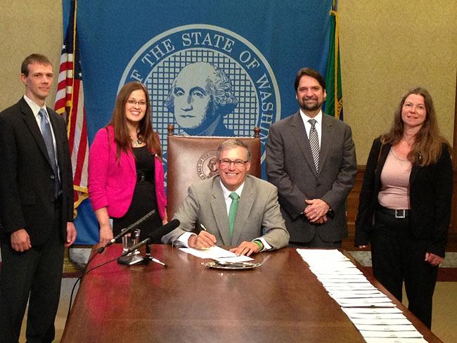 Governor Jay Inslee poses for a photo after a bill signing in Olympia.