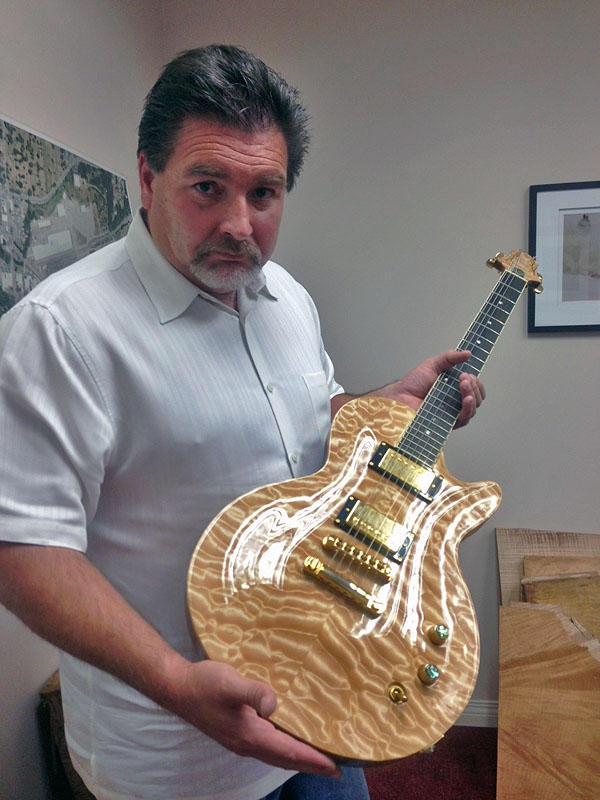 Former maple merchant Troy Dana holds a quilted maple-topped electric guitar he built himself.