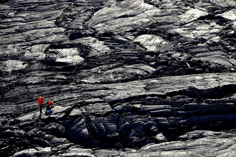 A pair of searchers works across a lava field at Craters of the Moon National Monument near Arco, Idaho.