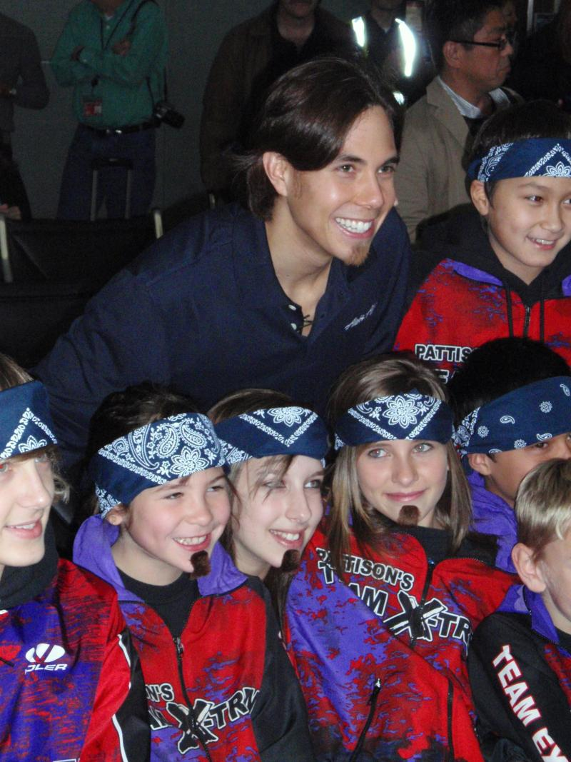 Olympic gold medalist Apolo Ohno poses with a younger generation of speedskaters from his original club team.