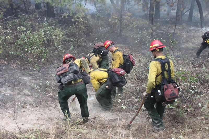 A National Interagency Fire Center spokeswoman says a hiring freeze will not affect firefighting operations.
