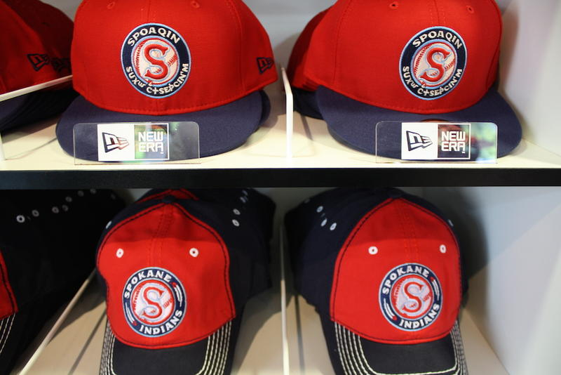 Hats in the Spokane Indians team shop with logos in English and Salish.