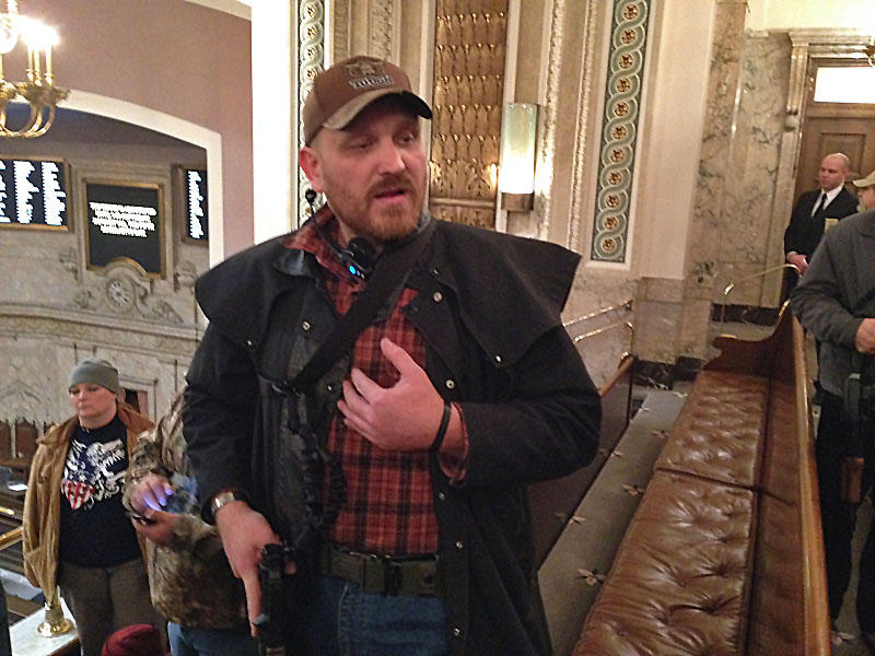 Jason McMillan carrying a military-style pistol in the Washington House gallery in 2015. Beginning in January of 2018, all guns will be banned from the Senate gallery.