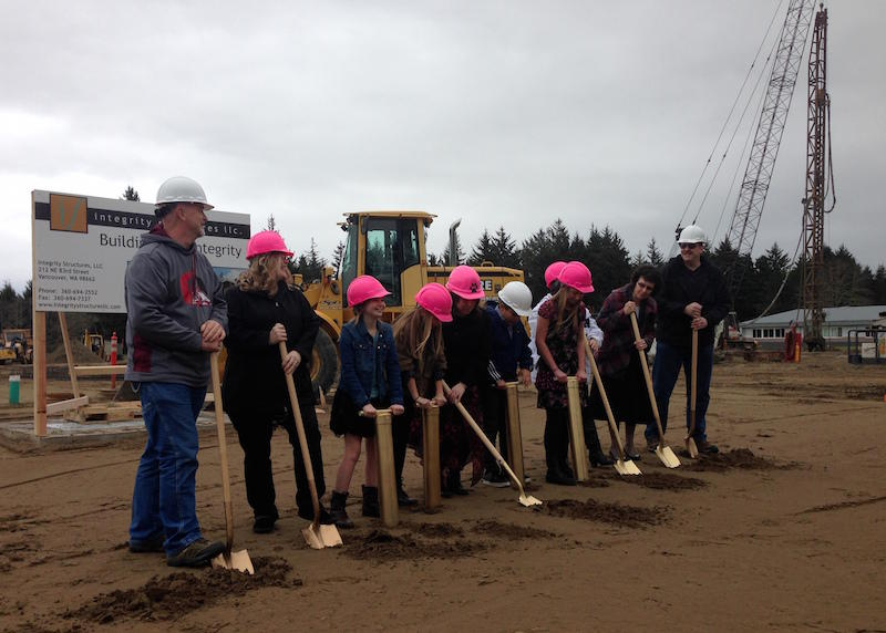 Ocosta Elementary students wielded clam guns while adults guiding the new school/tsunami refuge project shoveled at the groundbreaking ceremony Thursday.