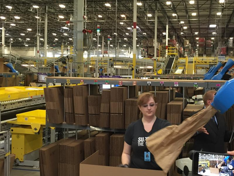 """Amazonians,"" the nickname for fulfillment center workers, performing packing and loading chores, which they can do better than robots."