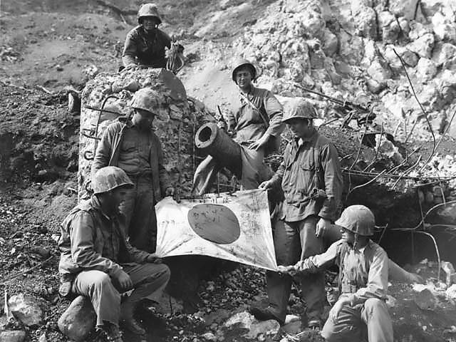 U.S. Marines pose with a captured Japanese flag on Iwo Jima.