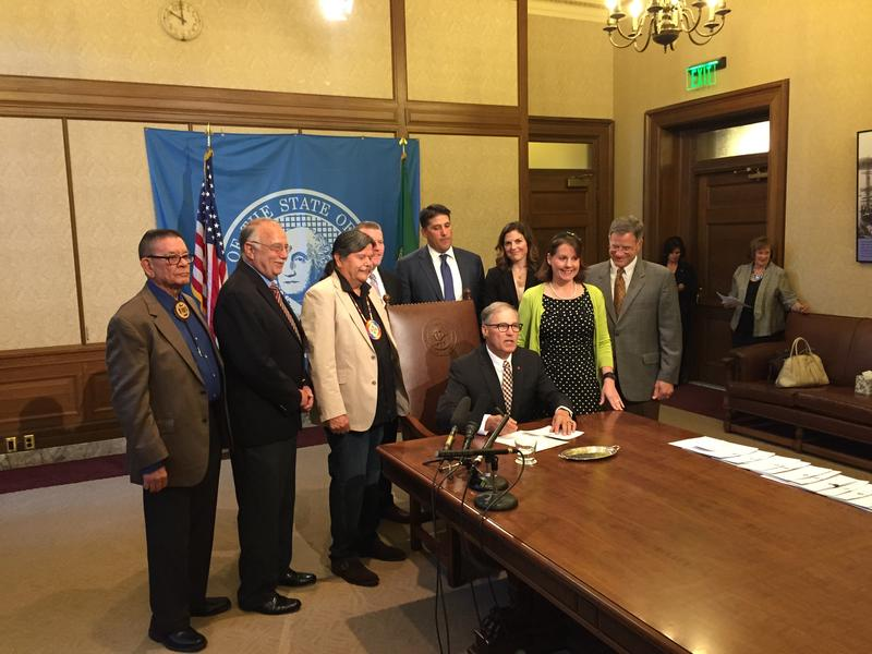 Puyallup Tribal Chairman Bill Sterud stands third from left behind Gov. Jay Inslee at a bill signing ceremony on Friday.