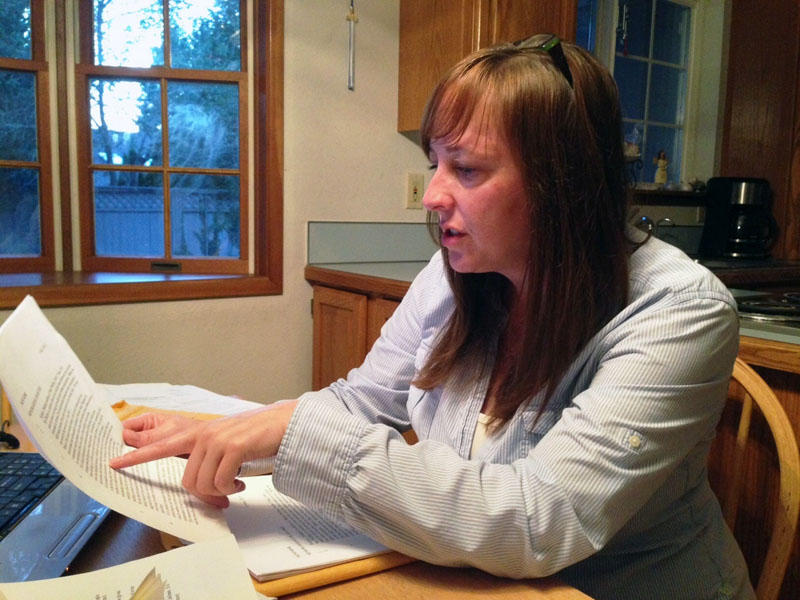 Karri Phillips sits at her kitchen table surrounded by medical and court records related to her son's traumatic brain injury and compromised mental health.