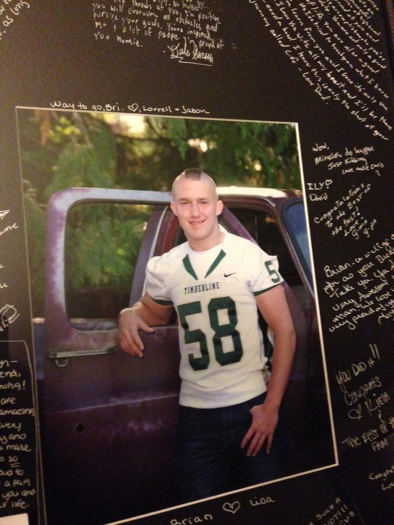 This high school graduation photograph of Brian Phillips, a former football player, hangs in his mother's living room. It includes messages from his family and friends.
