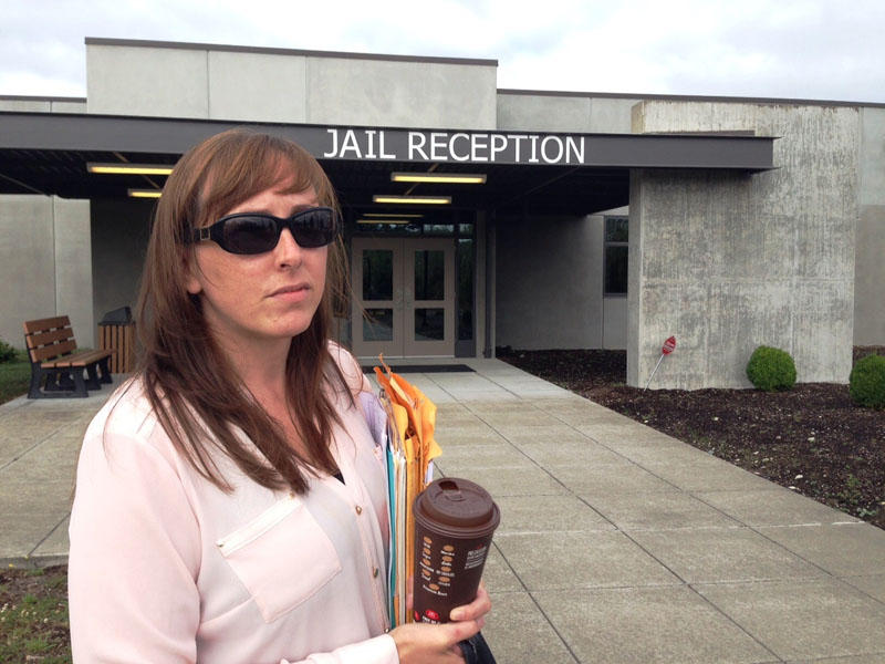 Karri Phillips stands outside the Thurston County Jail where her son has been held in isolation for more than 60 days.