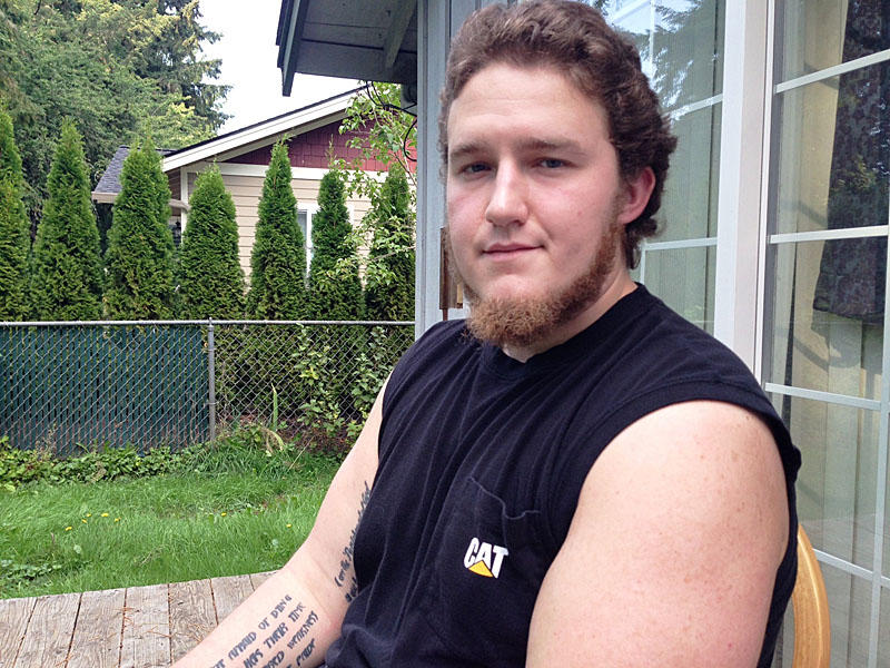Brian Phillips sits on the deck in the backyard of his mother's house in Lacey, Washington. This summer he was jailed after going off his psychiatric medicine and having run-ins with police. He was held for 71 days in isolation.